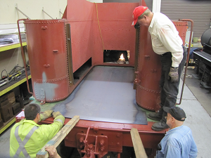 Ed Jr, Steve and Doug installing the sheet metal floor on the coal area of the tender.